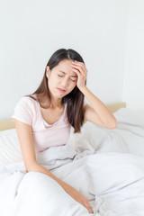 Beautiful woman having a headache sitting in bed
