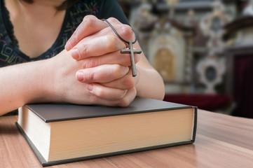 Praying woman holds cross in church.