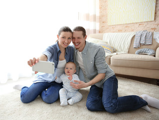Happy couple taking a selfie with baby in a living room, close up