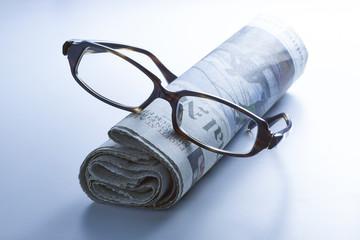 Glasses on newspaper , blue tone