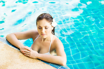 Beautiful woman relaxing in a pool at summer.