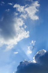sunbeam of sunlight through clouds on clear blue sky