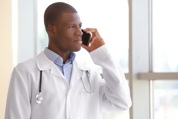 Handsome African American doctor talking on mobile phone in hospital