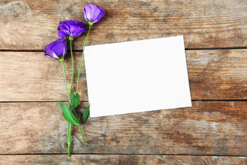 White sheet and violet blossom on wooden background, empty space