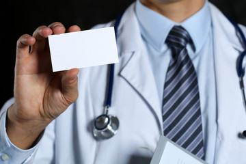 Male physician hand holding white blank calling card closeup