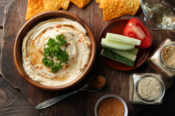 Wooden bowl of tasty hummus with chips, parsley on table
