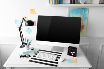 Modern wide screen monitor and lamp on white table in room interior