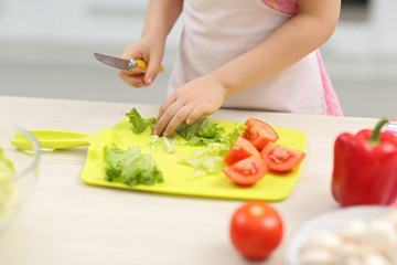 Little girl's  hands cutting vegetables on a board.