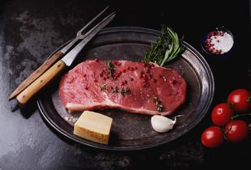 Raw striploin beef steak on black background