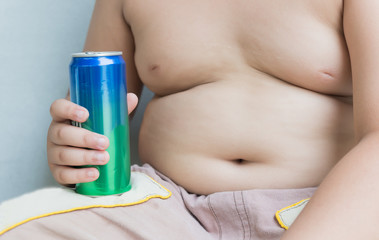 Diet. Obese fat boy holding soft drink can.