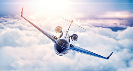 Picture of black luxury generic design private jet flying in blue sky at sunset. Huge white clouds background. Business travel picture. Horizontal, top view. 3d rendering