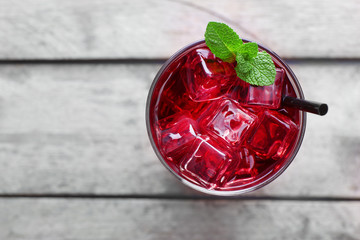 Glass of cherry soda with ice and fresh mint on rustic wooden background