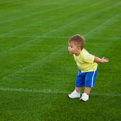 little funny boy on football field