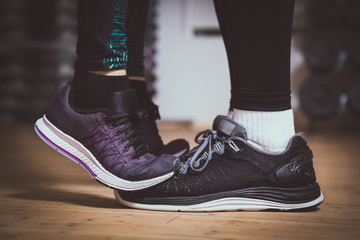 Closeup of sneakers. Girl standing on toes to kiss boyfriend. Couple workout concept. Love sports concept.