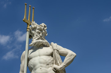 Neptun with a trident.Stone statue of a Greek God Poseidon against a blue sky. Nymphenburg palace, Munich,Germany