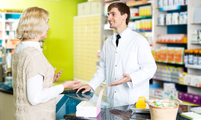Helpful pharmacist serving young woman in pharmacy