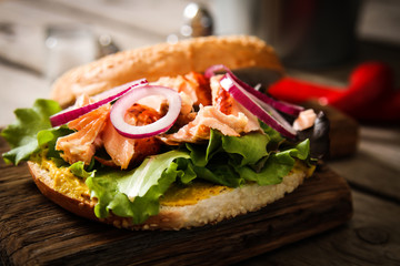 bagel with lettuce and baked salmon on a wooden board,