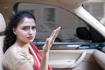 Frustrated Indian woman in the car at traffic jam
