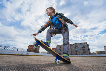 Happy small boy is going to skateboarding - people, sport and skateboarding concept.