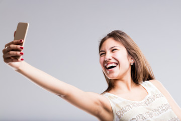 woman laughing at her mobile for a selfie
