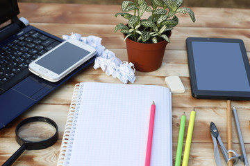 Laptop, smartphone, tablet, plant with financial documents on a wooden table