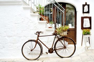 vintage bicycle against a wall in white city Ostuni, Apulia, Italy. - artistic picture italian style concept