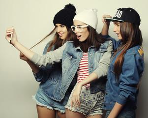 three happy teenage girls with smartphone taking selfie
