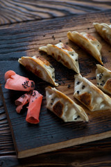 Closeup of fried gyoza served with black sesame seeds and ginger