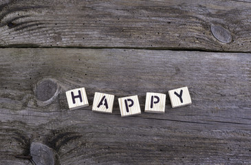 Text: Happy from wooden letters on wooden background