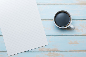 Coffee and notepaper on blue sky wooden floor.