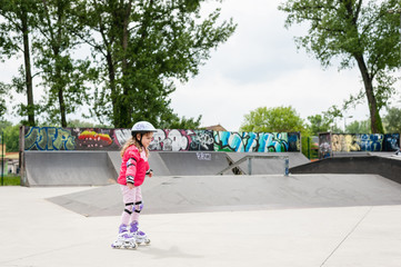 Little girl on roller skates in the skate park