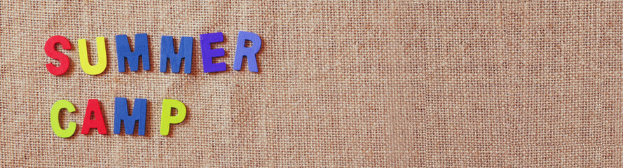 website banner of wooden letters with phrase: SUMMER CAMP