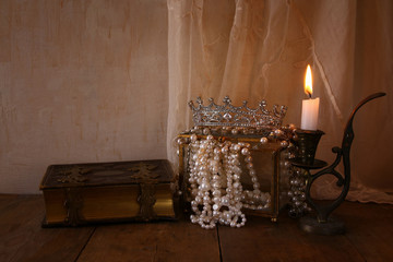 queen crown, white pearls next to old book