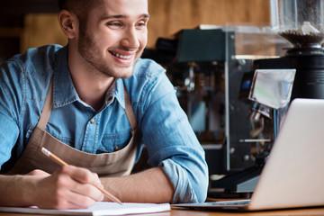 Joyful barista making notes
