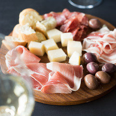 Traditional italian antipasto: white wine and plate with  prosciutto crudo, salami, parmesan cheese, olives and bread. Selective focus.