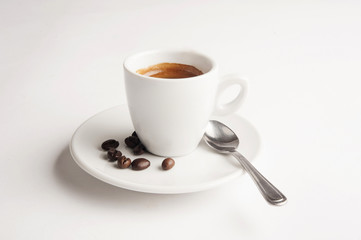 Cup of coffee on white background with spoon and coffee beans