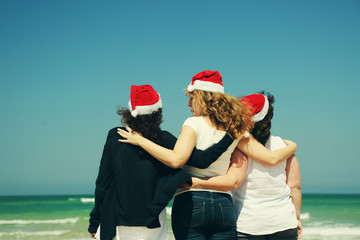 Three beautiful women wearing christmas hat walking on the seasi
