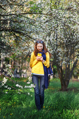 technology and people concept - smiling young woman texting on smartphone