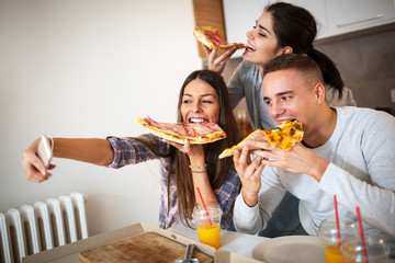 Young friends having party at home, eating pizza and smiling