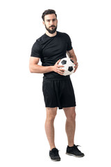 Confident soccer of futsal player holding ball with daring look at the camera. Full body length portrait isolated over white background.