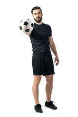 Football or soccer player holding and offering ball to a camera. Challenge concept. Full body length portrait isolated over white background.