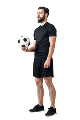 Football or soccer futsal player holding ball in one hand looking up. Full body length portrait isolated over white background.