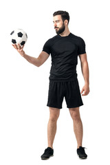 Determined challenging confident soccer player looking at the ball. Full body length portrait isolated over white background.