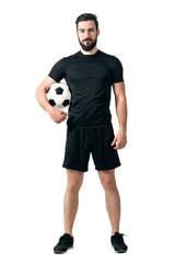 Smiling soccer or futsal player wearing black sportswear holding ball under his arm looking at camera. Full body length portrait isolated over white background.