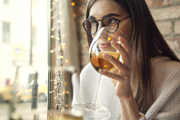 Woman in glasses drink white wine and having rest in cafe near window