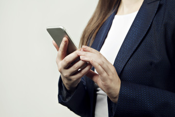 Close-up of woman hands hold phone, woman wears suit