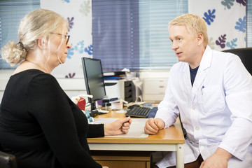 Doctor Communicating With Senior Patient At Desk