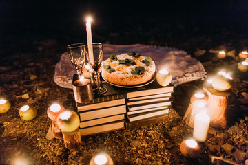 Romantic dinner with candles, cake and wine glasses at coast against wonderful night