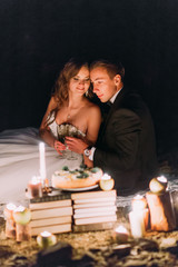 Loving couple share a romantic dinner with candles and cake  at beach, coast against wonderful night