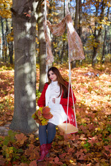 an expectant mother goes for a walk in the autumn park of swing